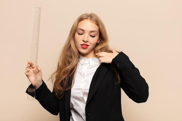 Blonde frau, die sich gestresst, ängstlich, müde und frustriert fühlt, hemdhals zieht und mit problem frustriert aussieht