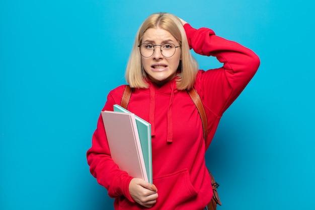 Blonde frau, die sich gestresst, besorgt, ängstlich oder verängstigt fühlt, mit händen auf dem kopf, die bei einem fehler in panik geraten