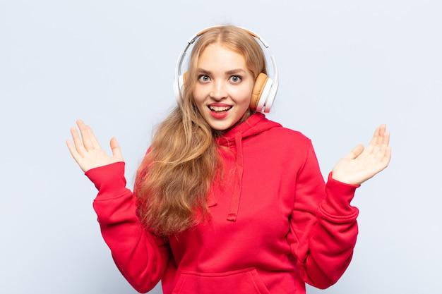 Blonde frau, die sich glücklich, aufgeregt, überrascht oder geschockt fühlt, lächelt und erstaunt über etwas unglaubliches
