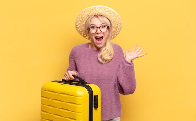 Blonde frau, die sich glücklich, aufgeregt, überrascht oder schockiert fühlt, lächelt und erstaunt über etwas unglaubliches