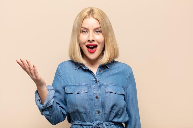 Blonde frau, die sich glücklich, überrascht und fröhlich fühlt, mit positiver einstellung lächelt und eine lösung oder idee verwirklicht