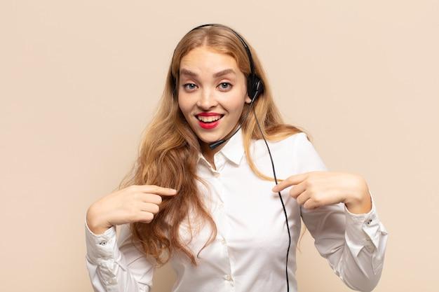 Blonde frau, die sich glücklich, überrascht und stolz fühlt und mit einem aufgeregten, erstaunten blick auf sich selbst zeigt