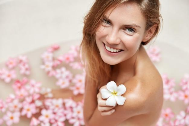 Blonde frau, die sich in der badewanne mit den blütenblättern entspannt