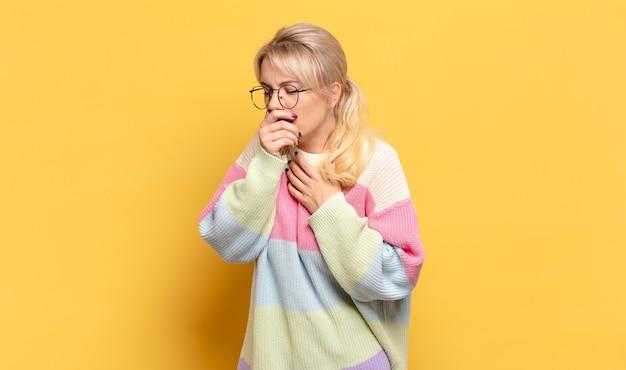 Blonde frau, die sich mit halsschmerzen und grippesymptomen krank fühlt und mit bedecktem mund hustet
