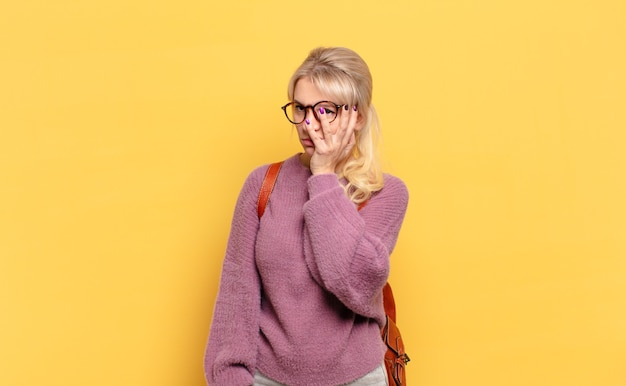 Blonde frau, die sich nach einer ermüdenden, langweiligen und mühsamen aufgabe gelangweilt, frustriert und schläfrig fühlt und das gesicht mit der hand hält