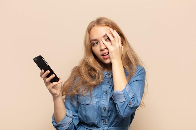 Blonde frau, die sich nach einer lästigen, langweiligen und mühsamen aufgabe gelangweilt, frustriert und schläfrig fühlt und das gesicht mit der hand hält