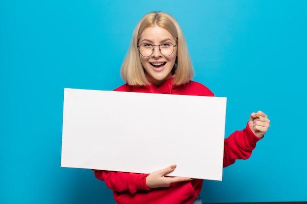Blonde frau, die sich schockiert, aufgeregt und glücklich fühlt, lacht und erfolg feiert