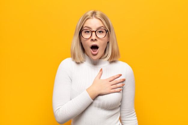 Blonde frau, die sich schockiert und überrascht fühlt, lächelt, sich die hand zu herzen nimmt, glücklich ist, diejenige zu sein oder dankbarkeit zu zeigen