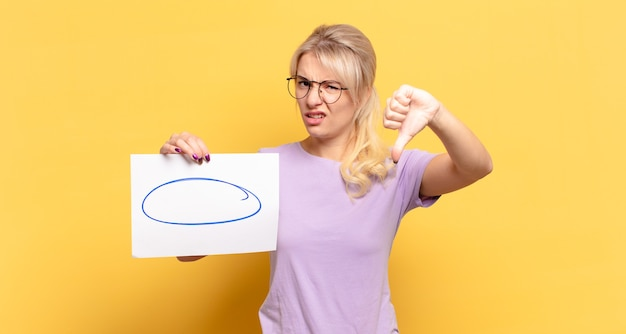 Blonde frau, die sich verärgert, wütend, verärgert, enttäuscht oder unzufrieden fühlt und mit ernstem blick daumen nach unten zeigt
