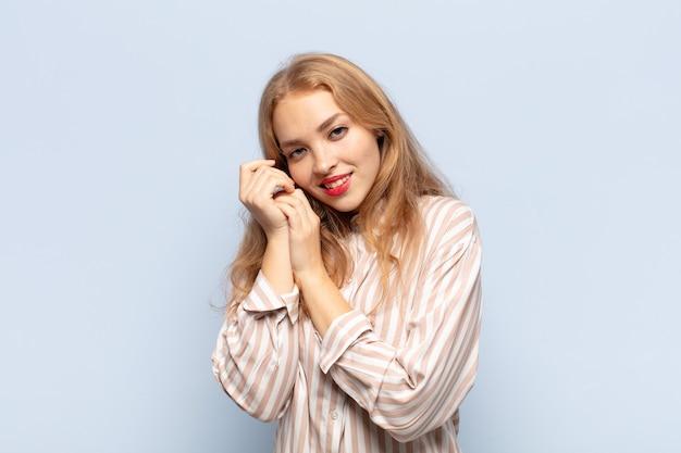 Blonde frau, die sich verliebt fühlt und süß, bezaubernd und glücklich aussieht, romantisch mit den händen neben dem gesicht lächelt