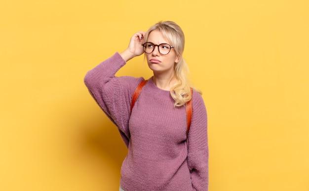 Blonde frau, die sich verwirrt und verwirrt fühlt, sich am kopf kratzt und zur seite schaut