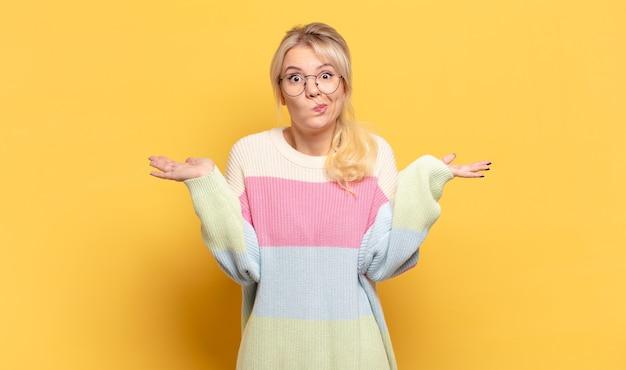Blonde frau, die sich verwirrt und verwirrt fühlt, zweifelt, gewichtet oder verschiedene optionen mit lustigem ausdruck wählt