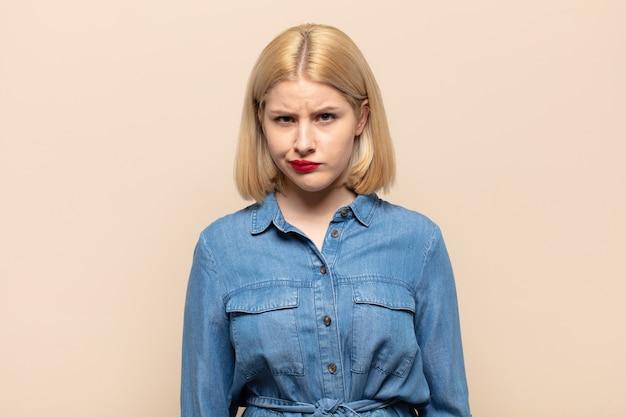 Blonde frau, die sich verwirrt und zweifelnd fühlt, sich wundert oder versucht, eine entscheidung zu treffen