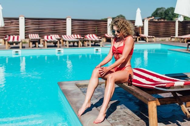 Blonde frau, die sonnenspray auf ihre beine aufträgt. frau sitzt auf einem liegestuhl am pool, der bräunungsöl auf ihre beine aufträgt.