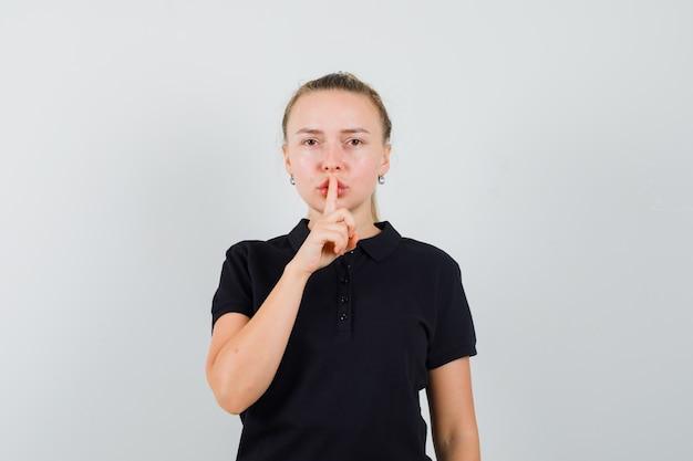 Blonde frau, die stille geste im schwarzen t-shirt zeigt und wütend aussieht
