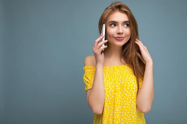 Blonde frau, die stilvolles gelbes sommerkleid trägt, das lokal über blauem hintergrund steht und auf handy hält, das zur seite schaut. freiraum