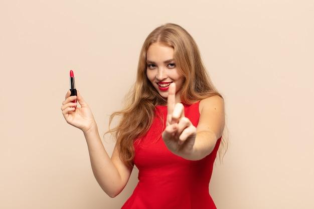 Blonde frau, die stolz und selbstbewusst lächelt und die nummer eins triumphierend posiert und sich wie ein anführer fühlt