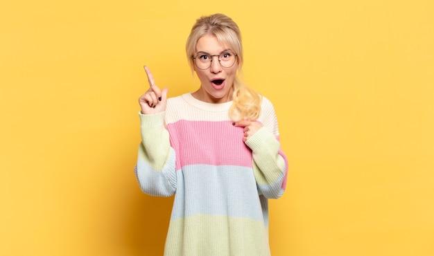 Blonde frau, die stolz und überrascht ist, selbstbewusst zeigt und sich als erfolgreiche nummer eins fühlt