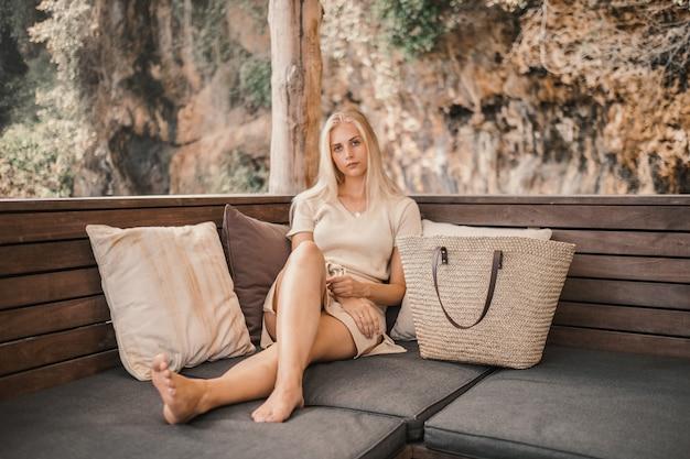 Blonde frau, die tagsüber neben ihrer tasche liegt