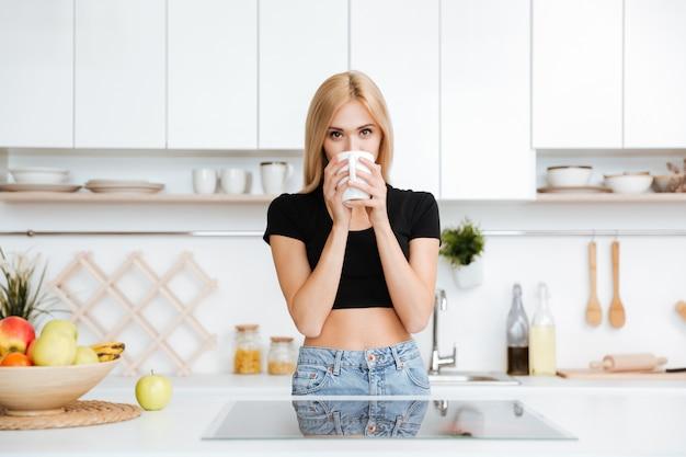 Blonde frau, die tee in der küche trinkt