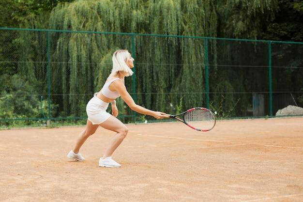 Blonde frau, die tennis spielt