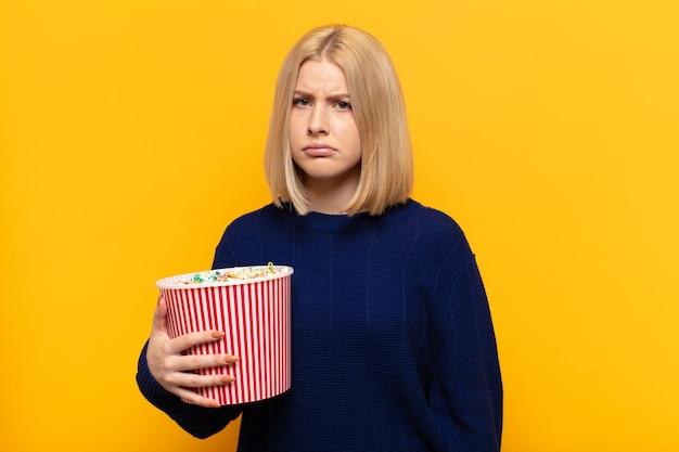 Blonde frau, die traurig und weinerlich mit einem unglücklichen blick fühlt und mit einer negativen und frustrierten haltung weint