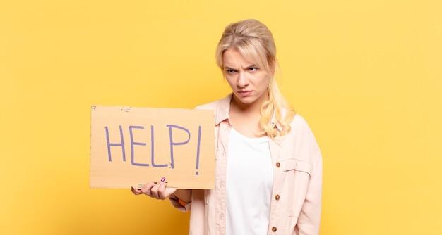 Blonde frau, die traurig, verärgert oder wütend ist und mit einer negativen einstellung zur seite schaut und vor uneinigkeit die stirn runzelt