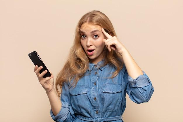 Blonde frau, die überrascht, mit offenem mund, schockiert aussieht und einen neuen gedanken, eine neue idee oder ein neues konzept verwirklicht