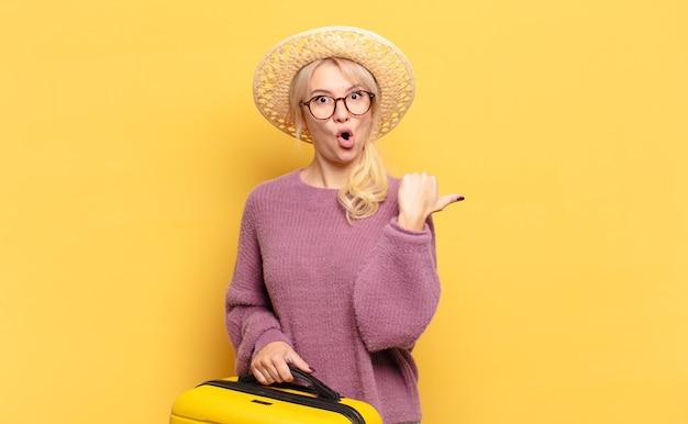 Blonde frau, die ungläubig erstaunt aussieht, auf einen gegenstand auf der seite zeigt und wow sagt, unglaublich