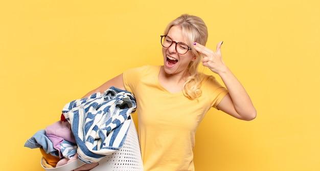Blonde frau, die unglücklich und gestresst aussieht, selbstmordgeste, die gewehrzeichen mit hand macht und auf kopf zeigt