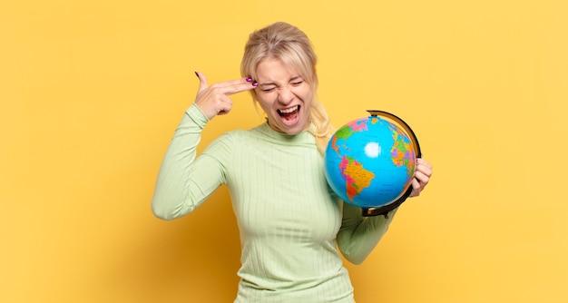 Blonde frau, die unglücklich und gestresst aussieht, selbstmordgeste, die waffenzeichen mit der hand macht und auf den kopf zeigt