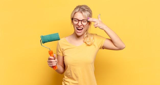 Blonde frau, die unglücklich und gestresst aussieht, selbstmordgeste, die waffenzeichen mit hand macht, zeigt auf kopf