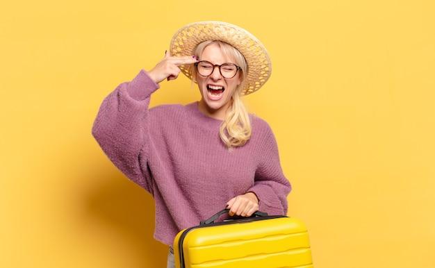 Blonde frau, die unglücklich und gestresst schaut, selbstmordgeste, die gewehrzeichen mit hand macht und auf kopf zeigt