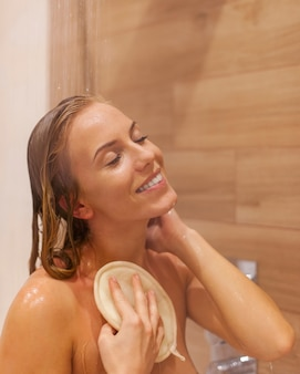 Blonde frau, die unter der dusche entspannt