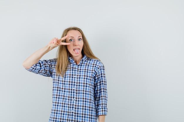 Blonde frau, die v-zeichen nahe auge zeigt, zunge in hemd herausstreckt und selbstbewusst aussieht,