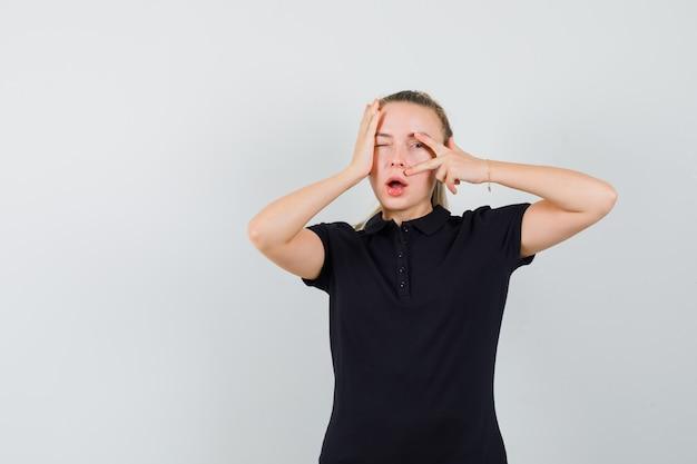 Blonde frau, die v-zeichen zeigt und ihre hand auf kopf in schwarzem t-shirt legt und optimistisch aussieht