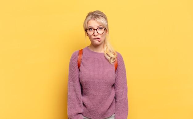 Blonde frau, die verwirrt und verwirrt aussieht, mit einer nervösen geste auf die lippe beißt und die antwort auf das problem nicht kennt