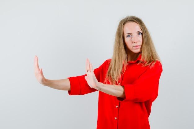 Blonde frau, die vorbeugende hände im roten hemd hält und vorsichtig schaut,