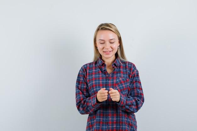 Blonde frau, die vorgibt, mit telefon im karierten hemd zu spielen und optimistisch, vorderansicht schauend.