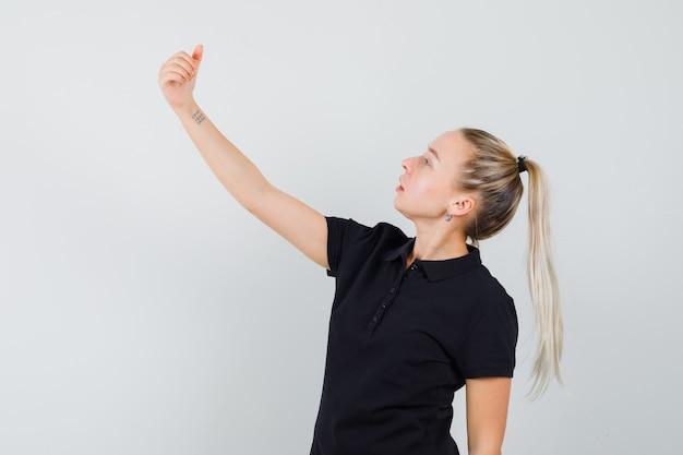 Blonde frau, die vorgibt, selfie im schwarzen t-shirt zu nehmen und optimistisch auszusehen