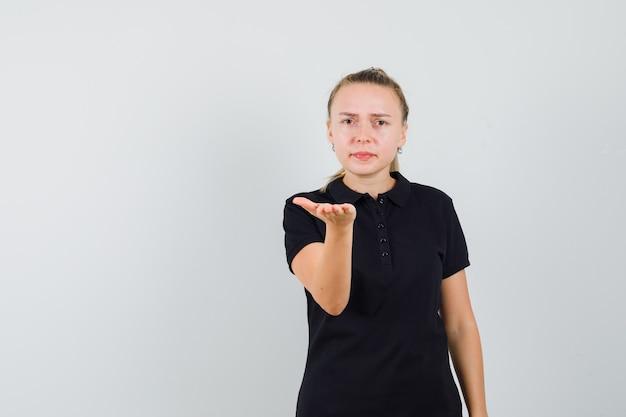 Blonde frau, die vorne im schwarzen t-shirt zeigt und ernst schaut