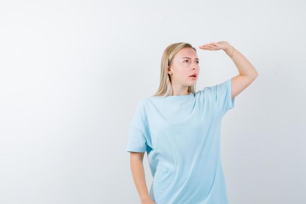Blonde frau, die weit weg mit der hand über dem kopf in blauem t-shirt schaut und konzentriert aussieht