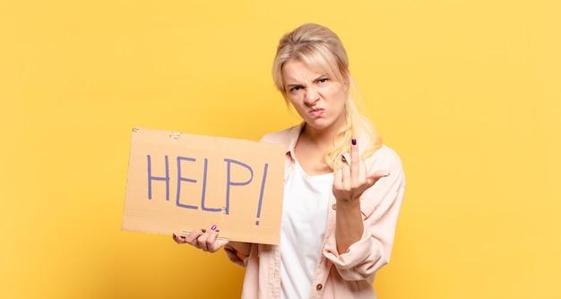 Blonde frau, die wütend, genervt, rebellisch und aggressiv ist, den mittelfinger umdreht und sich wehrt