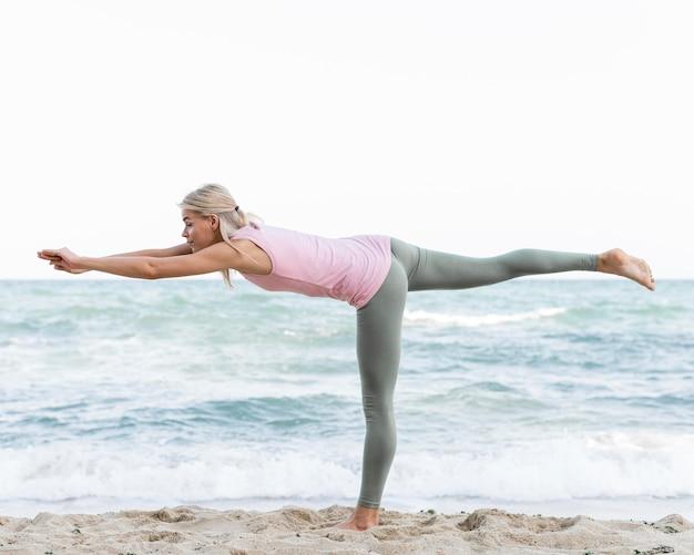 Blonde frau, die yoga am strand tut