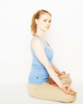 Blonde frau, die yoga-übung arbeitet