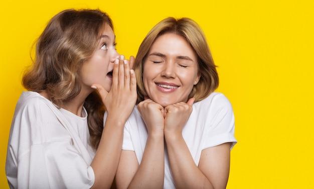 Blonde frau flüstert ihrer freundin etwas zu, während sie auf einer gelben studiowand posiert