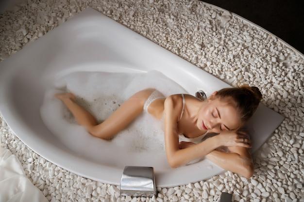 Blonde frau frau im badezimmer mit schaum. entspannen und
