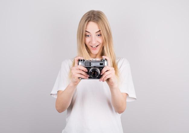 Blonde frau freudig überrascht, eine retro-kamera betrachtend