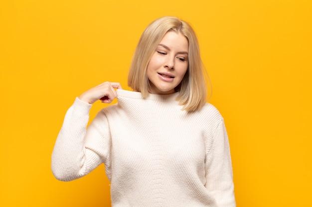 Blonde frau fühlt sich gestresst, ängstlich, müde und frustriert, zieht den hemdhals und sieht frustriert vor problem aus