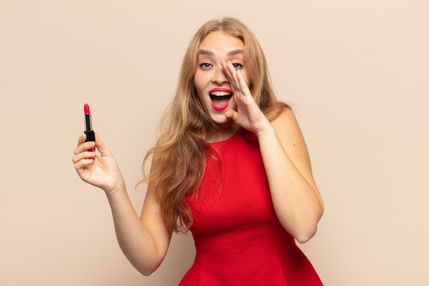 Blonde frau fühlt sich glücklich, aufgeregt und positiv, gibt einen großen schrei mit den händen neben dem mund und ruft